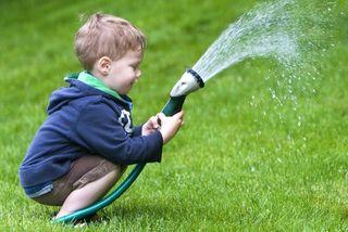 Boy Watering Lawn with Sprinkler
